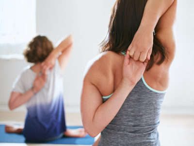 Women practicing gomukhasana in yoga class