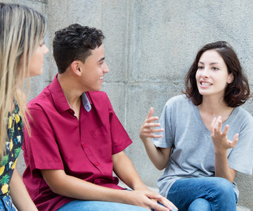 Three caucasian young adults in discussion