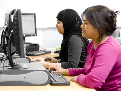 Two female college students use desktop computers.